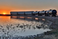 Prairie rail tracks are lit up by the setting sun in Saskatchewan.  Photo credit:  Lori Bote of Prairie Pixel Photography