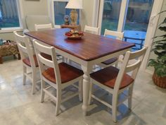 Rustic farmhouse table brown stained top, white painted legs, 6 white chairs, brown stained seats