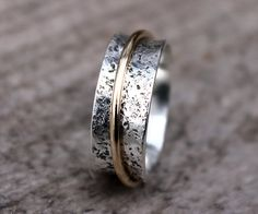 This hammered Argentium sterling silver spinner ring is a narrow spinner ring, at just about 1/4 in width, and is encircled by your choice of one captive 14K gold filled spinner, or sold gold spinner. This womens or mens spinner ring makes a gorgeous wedding ring, thumb ring. The bands flared edges keep the spinner in place, while allowing it to spin freely. The highly polished & textured sterling surface reflects the gold spinner beautifully. If youre looking for silver spinner rings…