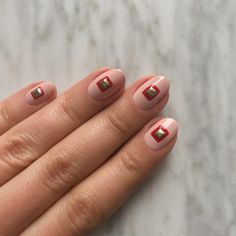 Trapped In A Box - If your go-to shade is a pale pink or subtle nude, try adding a graphic focal point to the center of eachnail. As always, start with a base coat, thenfollow with two coats of your favorite neutral polishand let themdry completely. Use a striping brush and red polish to draw a square in the center of every nail, then fill it in. Adhering with a drop of your base coat, carefully place a gold stud in the center of every square. Finish with a layer of topcoat.