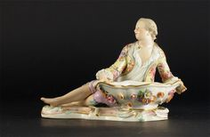 A Meissen figural sweetmeat, with a reclining man wearing a flowery coat, crossed swords mark.  Late 19th century