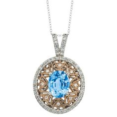 This uniquely styled 14K two-tone diamond pendant has an oval shaped blue topaz weighing 3.10 ct. surrounded by 0.62 ct. of brilliant diamonds. Made in USA by Variety Gem