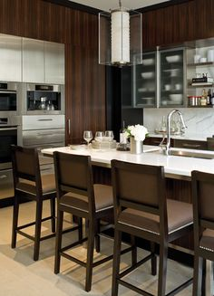 """Designer Brian Gluckstein chose dark Macassar ebony for the cabinetry, with a clean black """"frame"""" that sets off the rich wood. White counters and backsplash help keep the room light and airy. The 9′ x 4′ island houses the sink, dishwasher and a wine fridge. Stainless steel appliances and cabinetry break up the expanse of dark wood, keeping the look fresh."""