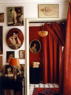 Bold art wall of vintage paintings in a dramatic red wall space - Gallery Wall Ideas & Decor
