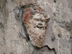 satyr mask in Herculaneum    Terracotta theatrical mask in the House of the Neptune Mosaic in the ruined ancient Roman city of Herculaneum near modern day Naples, Italy.    It depicts Silenus: an old, often drunken follower of Dionysus, who is often accompanied by satyrs.