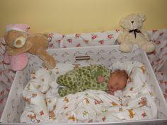 Newborn Finnish baby girl sleeping in a cardboard box.