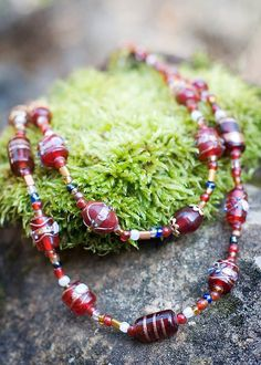 Sold. One of a kind. 21 inch, Red and Gold multi-strand necklace. Lampwork Beads strung with sections of large silver lined beads. Hints of blue, silver and shiny pearl like colors scatter throughout this piece. Lobster clasp and adjustable chain length. Www.etsy.com/shop/BlackRoseChris