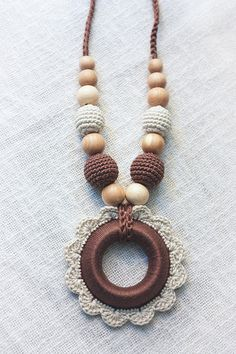 Babywearing Teething Nursing necklace for Mom with Crochet Pendant Wooden Ring flower Teether - Breastfeeding jewelry - cream purple brown _____________________________________________________  Stylish neutral nursing  teething necklace for breastfeeding moms! Your baby will enjoy chew necklace, touch crocheted beads, play with it. Nursing necklace help to evolve babys fine motor skills and keeps curious babies and toddlers from playing with moms hair or clothing. This eco-friendly necklace…