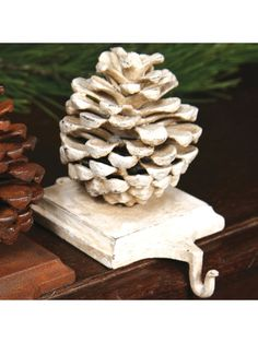 Seasonal decoration is perfect for bookcases or mantles. Constructed from cast iron to last for years. Lets you hang stockings without the use of screws or nails. Securely holds fully stuffed stockings. Cast iron, paint Imported the pinecone measures 3.5 in long 5.5 in wide 4.5 in high