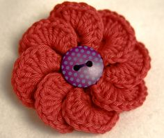 Pretty flower with button center: would be great on the hat I should crochet.