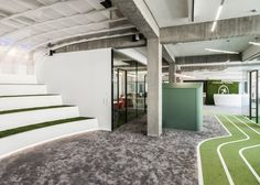 TKEZ architects have transformed a former factory into a football office/wonderland for Onefootball, with artificial tracks and turfs.