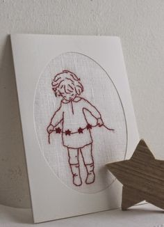 child with star garland red work embroidery
