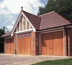 Triple garage with Garage Light and 2 Berkeley Vertical cedar timber garage doors Timber Garage Door, Garage Door Design, Garage Doors, Garage Lighting, House Front, Garages, Shed, New Homes, Outdoor Structures