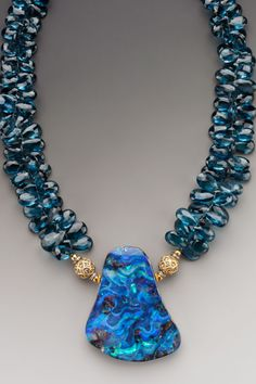 "Sea Nymphs's Grotto: A significant Australian boulder opal on large semi-transparent faceted briolettes of the finest London Blue topaz. 18K gold & diamonds, oxidized sterling silver & diamond marcasite accents. Pendant drop 2 1/2"". Pendant size 3 1/3"" x 2 1/2""."
