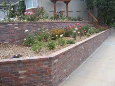 Retaining Wall with Brick Facade - I prefer my brick with a contrast material as the cap.  Dark slabs of smooth stone looks especially nice, but plain ole concrete is good, too.