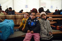 These refugee children from Afghanistan are seeking shelter from very cold, wet weather conditions at the Tabanovce reception centre for refugees in the former Yugoslav Republic of Macedonia after being refused entry into Serbia in February 2016.