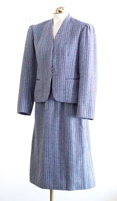 Womens tweed skirt suit from the 70s or 80s. The jacket is collarless and has a three small button front closure, and two front hip pockets. The sleeves are slightly puffed, and there is a two button faux closure at wrists. The fabric is a burgundy, blue, and gray herringbone tweed with vertical pinstripes. The sheath skirt of matching fabric falls below the knee. It has two side pockets and a back zip and flat hook and eye closure.  MEASUREMENTS (laid flat; approximate):  JACKET: Shoulder…