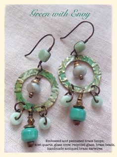 I embossed brass hoops, patinated them, and added a dangle of beautiful pale green kiwi quartz and antiqued brass beads inside the hoop. The bottom dangle of green glass and brass beads is surrounded by antiqued brass chain and green recycled glass. The recycled glass beaded brass earwires are ha...
