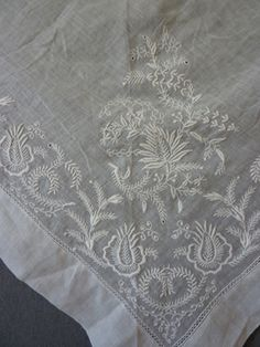 Triangular Fichu - Early 19th century - likely English Two longer sides embroidered with largish stylized flowerheads, curling leaves and small c scrolls, all in white cotton above drawn threadwork, on fine cotton ground Meg Andrews