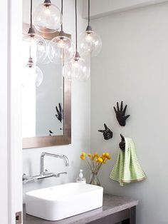 Work of Art The organic shape of this blown-glass light fixture works well in the contemporary-style bathroom. Modern spaces can feel cold and be full of hard edges, but the round globes on the light fixture and the hand-shape towel hooks in this bathroom add a touch of playfulness.