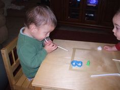 Toddler Science: Teaching heavy and light by blowing objects with straw