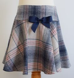 Blue check wool skirt Description: pretty circular style giving it a lovely fullness, contrasting grosgrain ribbon bow in navy or burgundy, concealed zip at side, elastic waist Sizes: available exclusively in 8y £36