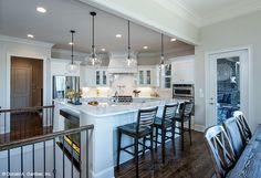 This angled kitchen features a center island with bar seating. The Monarch Manor house plan 5040. #WeDesignDreams