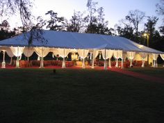 White tent with leg drape, bamboo folding chairs and red carpet.