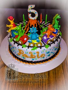 Colorful dinosaur train cake. Covered and decorated with fondant, buttercream...