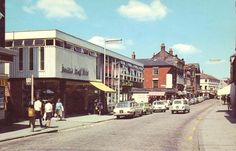 Kettering High Street. Freeman Hardy Willis on the left hand side. Granada Cinema is just out of picture. Meadow Road goes off to the left in the middle of the picture.