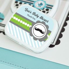 Little Man Party Personalized Mint Tins. Create your own unique baby shower with these personalized Little Man Mint Tins. These mint tins are just the right size for small candies, and guests can easily slip them into pockets and purses to take on the go. These versatile, white favor tins make the perfect thank you gift that will coordinate perfectly with your event décor. Blue and green personalized labels feature a classic mustache design, perfect for a celebrating your little...