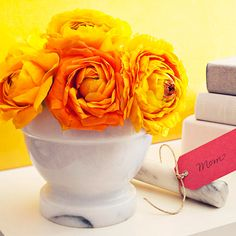 Spice of Life: For the chef, a marble mortar plays host to a small clutch of orange-yellow ranunculus. Cut the stems to 6 inches, and arrange them in a low, tight dome. Tie a gift tag around the pestle.