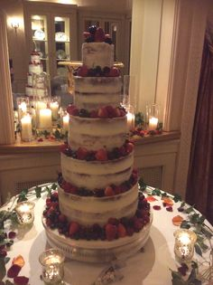 5 tier semi naked cake decorated with fresh berries and displayed surrounded by sumptuous candles and winter foliage for this Christmas wedding