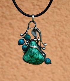 Zelený+sen+-+malachit+Šperk+je+vyroben+cínováním.+Je+tvořen velikým 3+x 3+cm+velkým+trojúhelníkovým malachitem. Jeho+krásná,+typicky+tmavá+zelená+barva+má +na+sobě+ještě+tmavší+malachitovou+kresbu. Jako+doplněk+do+kompozice jsou+vloženy korálky+chryzokolu,+které+dodávají+šperku+něžnost. Šperk je romantický+a+jemný.+Celý+šperk+je+veliký 7+...