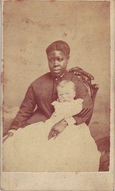 A Black woman holding a White child