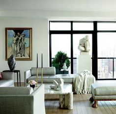 Artfully composed living room with chunky marble table and no rug