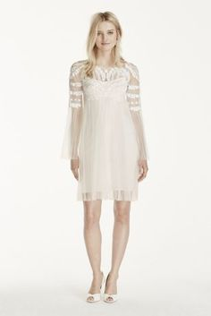 This unique dress is a must have for the modern chic bride to be!  Tulle dress features long illusion sleeves with cropped bodice adorned with elaborate embroidery.  Short above the knee tulle skirt with empire waist.  Sizes 0-14. Available in Ivory.  Fully lined. Back zipper. Imported. Dry clean only. To preserve your wedding dreams, try our Wedding Gown Preservation Kit.
