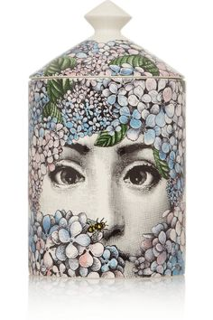 Fornasetti's scented decorative object is printed with the face of the Italian artist's muse Lina Cavalieri in the guise of the goddess Flora. The hand-poured candle is infused with a delicate White Rose and Jasmine aroma, created by perfumer Emmanuel Philip in homage to the luscious gardens of the Fornasetti's Milanese home.