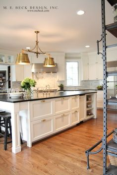 Kitchen with white cabinets, gray backsplash, and gold light fixture
