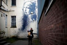 A woman photographs herself with a piece of street art attributed to Banksy after it was defaced in an alleyway in Bristol, England Provided by Reuters