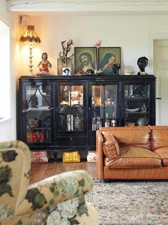 FRODIG MIKS: Det svartmalte skapet er et auksjonskupp. Bildene har beboerne arvet. Sofaen er også kjøpt på auksjon. Her finnes også flere afrikanske kvinnehoder - en av beboernes samlemanier.