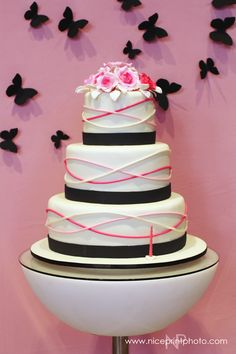 Shades of pink against a stark white cake. Add black bands for a bit of sophistication.
