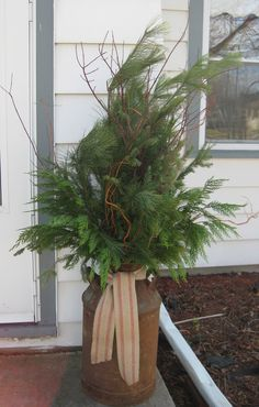 Old milk can, dog wood, curly willow, fresh boughs and burlap ribbon.