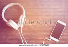 White phone and headphones on wooden table. Warm orange pink light toned photo. Smartphone and earphones vintage banner template with place for text. Music listening concept image. Hipster flat lay