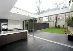 Modern extension to a listed terraced house in St Johns Wood, London. entire wall opens up to the garden and roof light brings in light throughout the day. Stacking Doors, Architects London, Clifton Hill, Glass Extension, John Wood, Timber Door, Residential Architect, Planning Permission, Roof Light