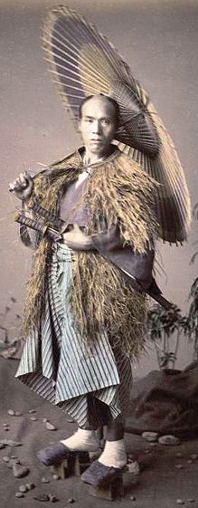 Samurai wearing a mino (straw rain cape) and holding an umbrella