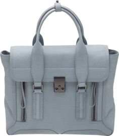 Cloud blue pebbled calf leather medium 'Pashli' bag from 3.1 Phillip Lim featuring a short front flap closure with clasp fastening, two top handles with top tab fastening, and front zip fastening extendable panels.