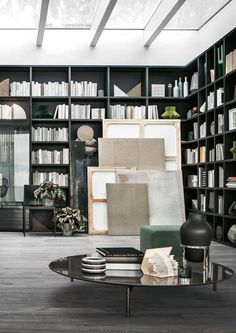LEMA | SELECTA Custom Made bookcase is the first product that combine the details of manual work on wood to a series of technical innovations that confer it maximum versatility in terms of compositions, uses and finishes. A large C-shaped bookcase in Carbone oak with corner systems alternates open shelving with units enclosed by elegant clear glass doors of different sizes with bronze anodized aluminum framing.