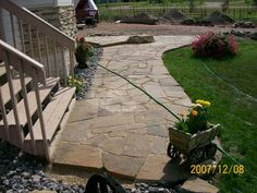 This country yard on an acreage looks much more at home with a dry-laid flagstone walkway from the gravel driveway to the front door.