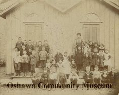 Sepia photograph mounted on dark cream coloured cardboard. The photograph shows the students of Cedardale Public School posed outside of the school with their teacher.
